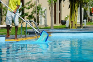 man cleaning the pool - swimming pool contractors san diego
