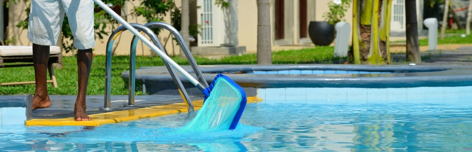 A man cleans the pool - swimming pool contractors