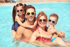 Family in the pool - swimming pool contractors near me
